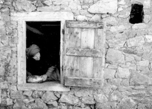 A woman appears in an open window in a stone house.